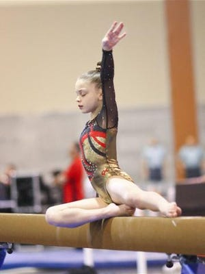 Annie Beard, 10, a Level 9 gymnast, performs a routine on the balance beam. She is also skilled in uneven bars, vault and floor.