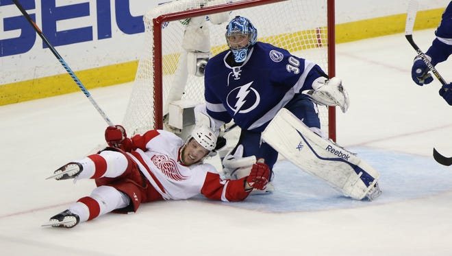 The Detroit Red Wings' Justin Abdelkader, left, collides with Tampa Bay Lightning goalie Ben Bishop (30) in the crease during the second period in Game 7 in the opening round of the Stanley Cup playoffs at the Amalie Arena in Tampa, Fla., on Wednesday, April 29, 2015.