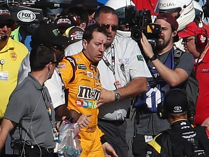 Kyle Busch, driver of the No. 18 M&M's Toyota, is escorted