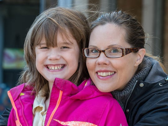 Ava Vidovich, 7, poses for a photo with her mother Melanie Hicks at the downtown Salisbury rock garden on Monday, Nov. 20, 2017.