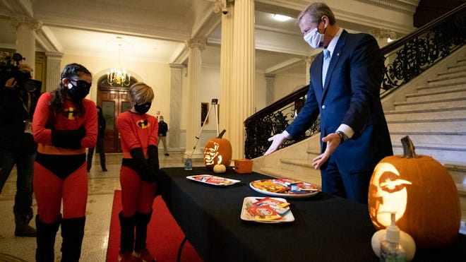 Gov. Charlie Baker invited Emily Van Rhijn and Piper Abbett, 11, of Sherborn to choose from an array of king-sized candy bars Friday morning at the State House's Grand Staircase.