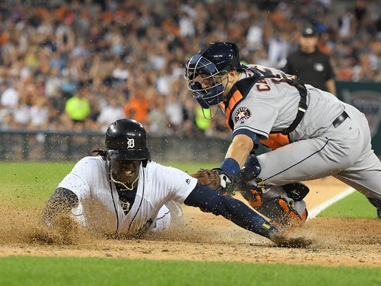 Tigers centerfielder Cameron Maybin, left, dives safely into home ahead of the tag by Astros catcher Jason Castro to score a run in the sixth inning Saturday at Comerica Park.