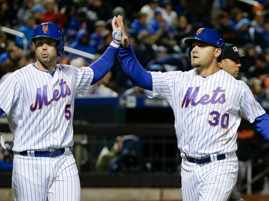 New York Mets' David Wright (5) high-fives teammate Michael Conforto (30) after the two scored against the San Francisco Giants during the third inning of a baseball game, Friday, April 29, 2016, in, New York. (AP Photo/Julie Jacobson)