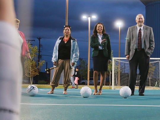 Dignitaries, including Elaine Williamson, right, widow of John Lyons, prepare to kick a ball into a soccer goal as part of Thursday's ceremony to dedicate John Lyons Park. Lyons was instrumental in turning what was formerly a dump site into a modern park.