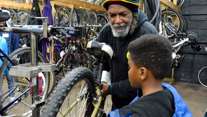 Freewheelin' staff member Achebe Lateef helps adjust a bike part during the Earn-A-Bike program. Lateef was one of the first staff members hired in 2007.