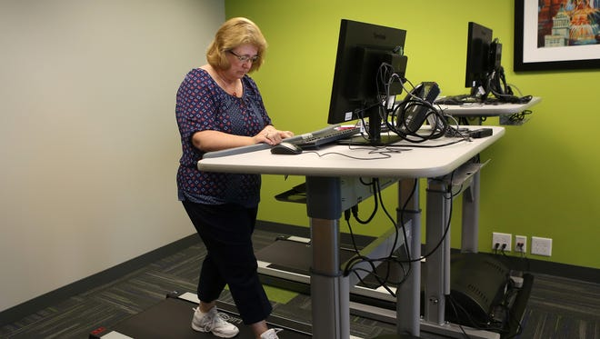 Employee Sharon Lippolis walks on a treadmill as she works on a computer at Ohio National.