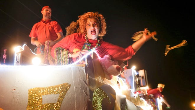 Float riders throw beads during the Friday Night Mardi Gras Parade Friday, Feb. 24, 2017 in downtown Lafayette.