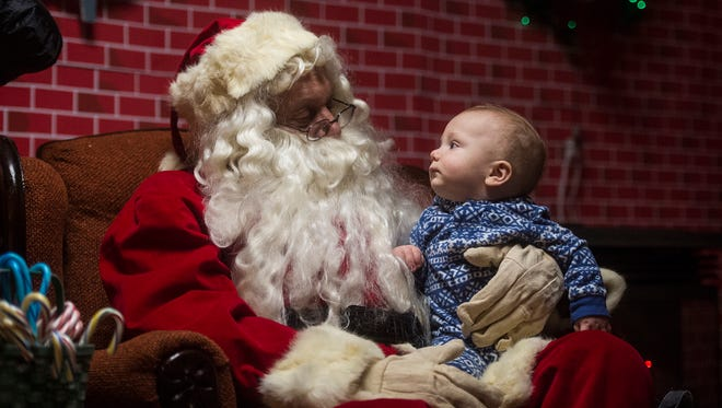 Drew Piper, eight months, of Gettysburg, looks Santa straight in the eye on Dec. 6, 2015 at Santa's Workshop at Artillery Ridge Campground outside of Gettysburg. Piper's mother, Stacee Piper, said this was the first time her son got to meet Santa.