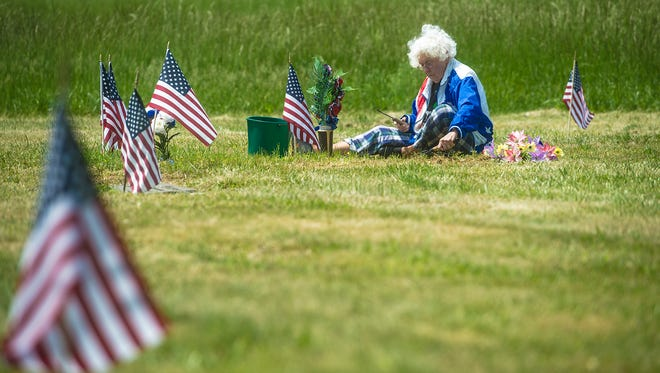 Marian Berry of Carlisle uses a garden trowel to straighten the area around her husband's grave in 2016 at Oak Lawn Memorial Gardens. On Monday, victims of former Oak Lawn owner James Delaney were given the chance to speak in court before Delaney was sentenced. He pleaded guilty Oct. 6 to two charges related to the mismanagement of the cemetery and its funds.