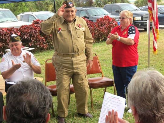 World War II Veteran Joe Celli salutes the crowd during an awards ceremony Jan. 20 at VFW Post 10066 in Jensen Beach. Applauding with the crowd were VFW Chaplain Paul Little, left, and Celli's wife, Barbara Celli, right.