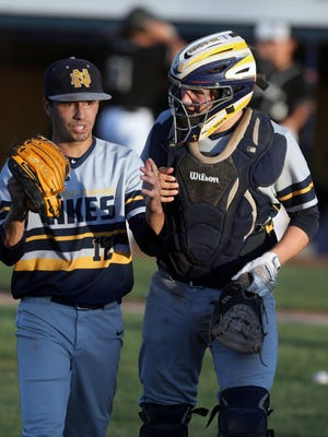 In this file photo Notre Dame High School catcher Trenton Blythe heads back to the dugout with pitcher Nicholas Skerik during a Class 1A district quarterfinal against Pekin High School July 16, 2019 at Notre Dame's Winegard Field.