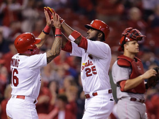 St. Louis Cardinals' Dexter Fowler (25) celebrates with Kolten Wong (16) after hitting a two-run home run, as Cincinnati Reds catcher Devin Mesoraco looks towards the field in the third inning of a baseball game, Friday, April 28, 2017, in St. Louis. (AP Photo/Tom Gannam)