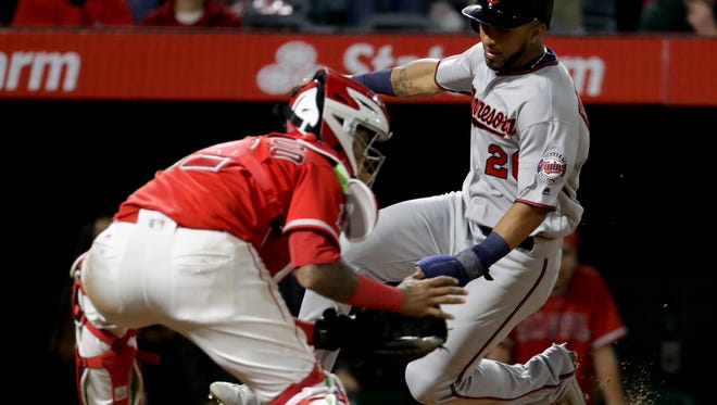 Minnesota Twins' Eddie Rosario, right, scores past Los Angeles Angels catcher Martin Maldonado on a hit by Jason Castro during the ninth inning of a baseball game in Anaheim, Calif., Thursday, June 1.