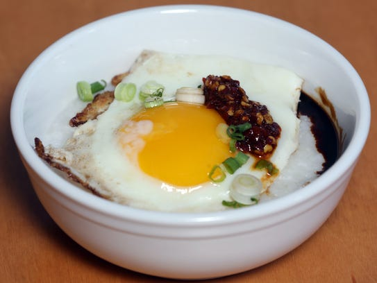 Rice porridge with fried egg, chili paste and dark