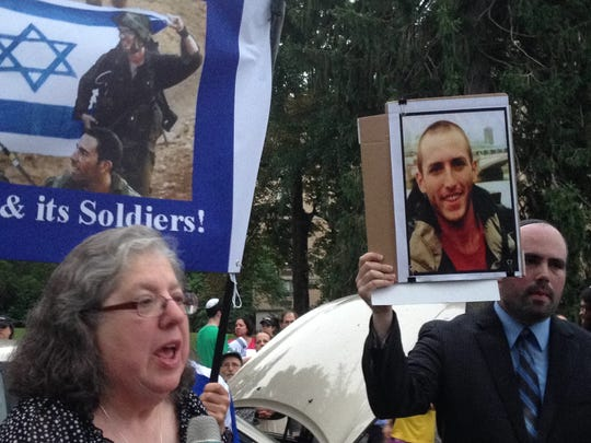 Rhoda Cohen, right, of East Brunswick speaks at rally on Wednesday in Highland Park co-organized by Josh Fine, left, of Highland Park. Fine is holding a photo of Cohen's nephew, a soldier with the Israeli Defense Force who was killed in battle on Monday.