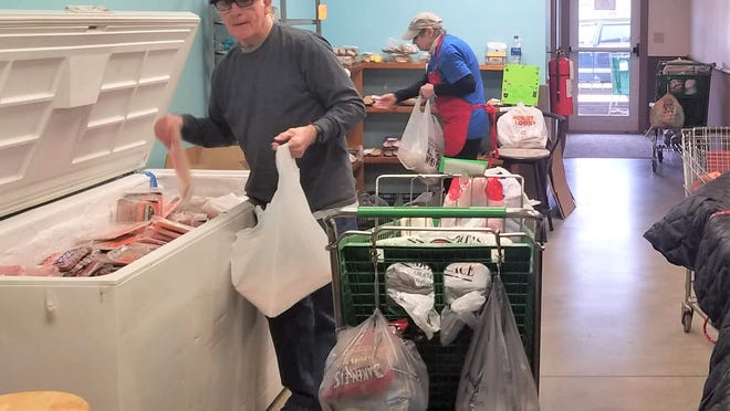 Volunteers Bill Morrison fills frozen meats and Michelle Alexander gives breads and desserts fill bags for people in line at the Love Center Food Pantry in Millersburg.