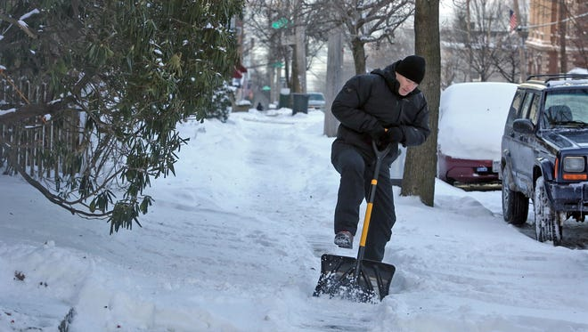 An Irvington resident gives his shovel a good kick as he breaks through the ice while shoveling in front of his home.