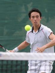 Japan's Keisuke Numajiri approaches the net for a forehand