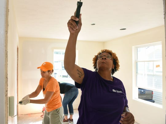 Homeowner Whitnee Holloway works alongside wives of coaches from the University of Tennessee football program as they painted the walls on her Habitat for Humanity home she will purchase Wednesday, Jul. 26, 2017.