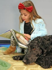 "Ariana LeGrant, 6, of Clive reads to Justice the Labradoodle therapy dog during ""Tales with Tails"" reading event with a dog visitor on Saturday, Dec. 16, 2017, at the Clive Library."
