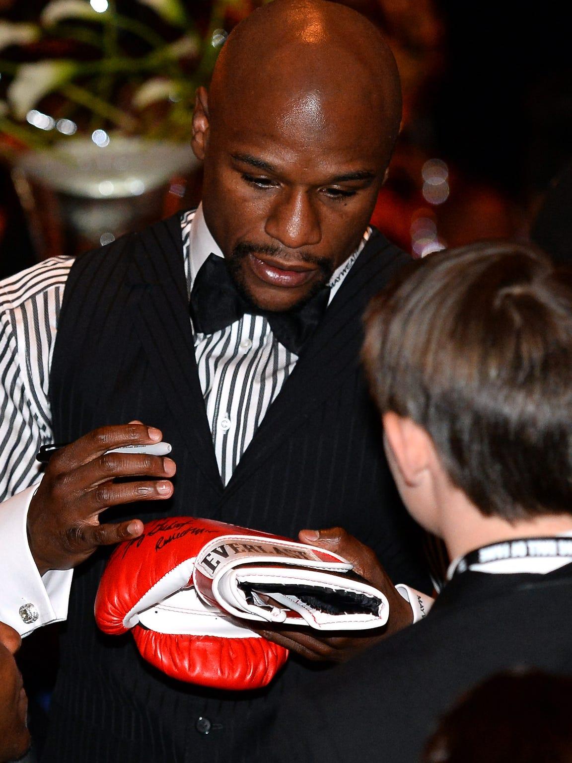 El boxeador Floyd Mayweather Jr. firma un autógrafo a un fanático.