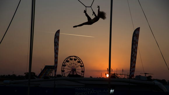 An acrobatic entertainer swings high above the fair grounds as the sun begins to set Monday, March 19, 2018 in Naples.