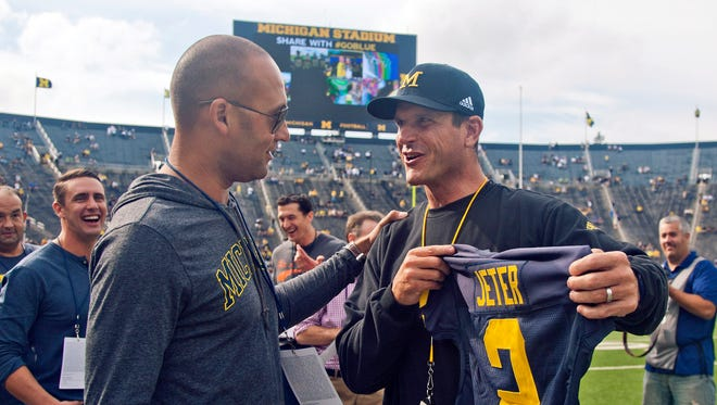 Former New York Yankees baseball player Derek Jeter, left, receives a jersey with his name an No, 2 from Michigan head coach Jim Harbaugh, right, before Michgan's NCAA college football game against BYU in Ann Arbor, Mich., Saturday, Sept. 26, 2015.