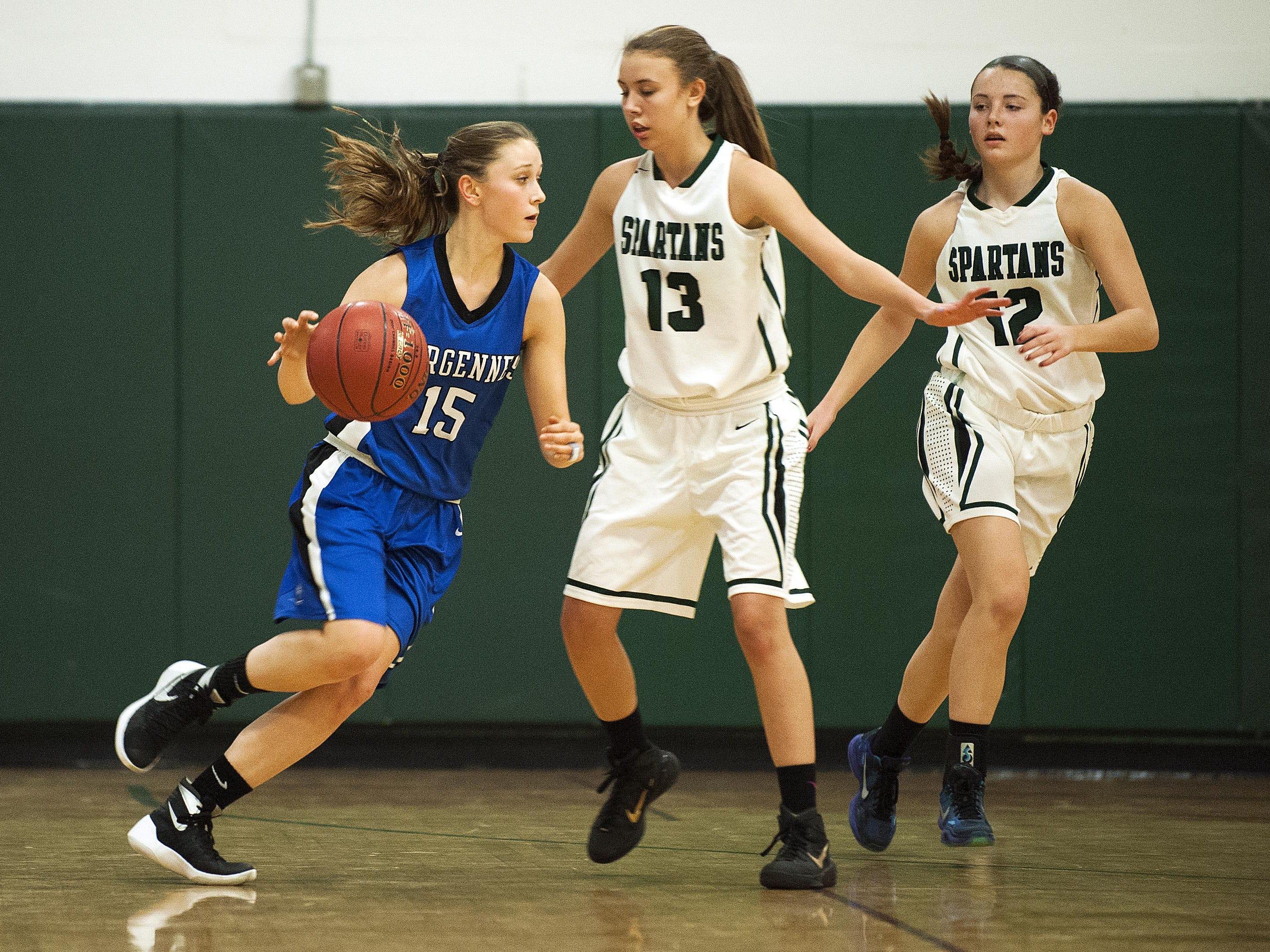 Vergennes' Caroline Johnston (15) tries to dribble then all around Winooski's Riley Corrigan (13) during the girls basketball game at Winooski High School on Wednesday night.