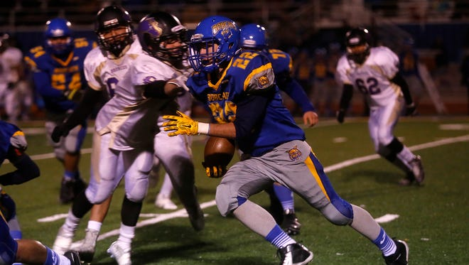 Bloomfield's Chauncey White carries the ball during Friday's game against Kirtland Central at Bobcat Stadium in Bloomfield.