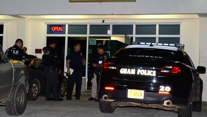 Guam Police Department officers investigate an armed robbery at Lucky Land in Dededo, Guam, on Oct. 8, 2014.  News/mwatanabe@guampdn.com