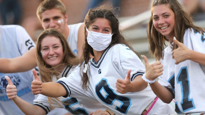 Louisville fans Cory Noble (far let), Erika Joseph (second from left), Amanda Vesely (center) and Emilee Mueller gave thuumbs up to a new high school football season during their game at Dover on Thursday, August 27, 2020.