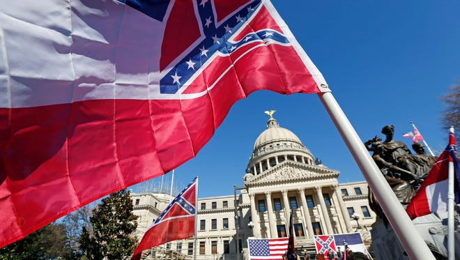 In this file photo, Sons of Confederate Veterans and other groups parade on the grounds of the state Capitol in Jackson, Miss., Tuesday, Jan. 19, 2016, in support of keeping the Confederate battle emblem on the state flag.