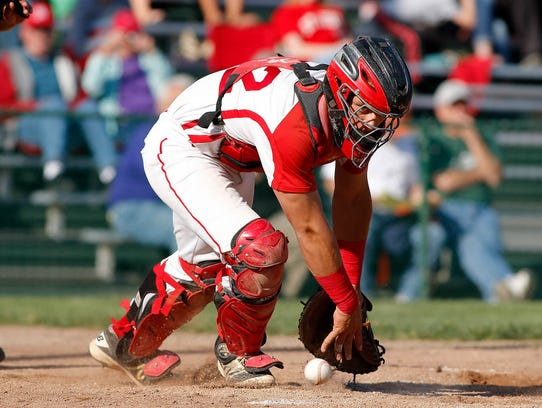 St. Johns catcher Adam Proctor chase down a low pitch
