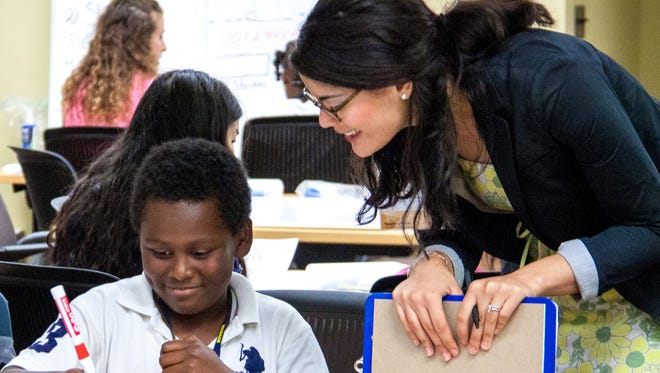 Elizabeth Davila-Ferrall, right, a student at U-M's School of Education, takes part in some of her required work in a classroom.