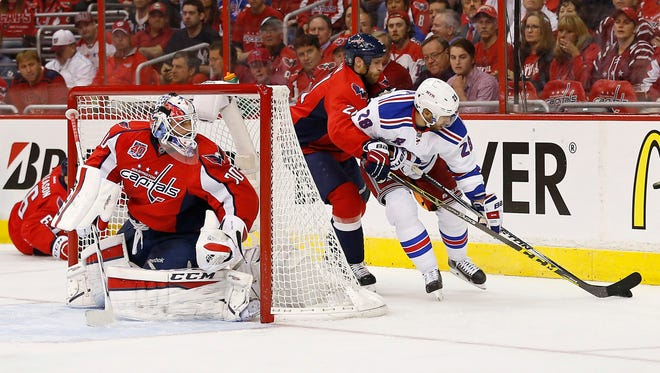 Capitals goalie Braden Holtby watches Rangers center Dominic Moore and Capitals center Brooks Laich (21) battle for the puck behind the net.
