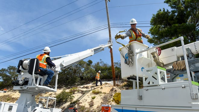 Pacific Gas and Electric Company workers from California hoist fallen power lines Wednesday, Sept. 13, 2017, just south of the Hobe Sound National Wildlife Refuge off of U.S. Highway One in Hobe Sound.
