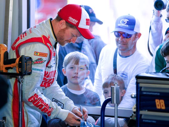 Driver Dale Earnhardt Jr., left, signs autographs for fans at his garage during practice for the NASCAR Daytona 500 auto race at Daytona International Speedway in Daytona Beach, Fla., Feb. 15, 2014.