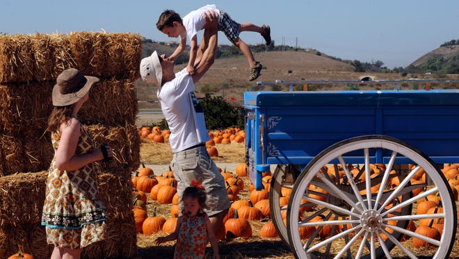 Ventura residents Susan Sharma (left) watches her husband Ryan Sharma help their son Ethan off a wagon that he and his sister Eliana played on at the Fall Harvest Festival at Underwood Family Farms in Moorpark.