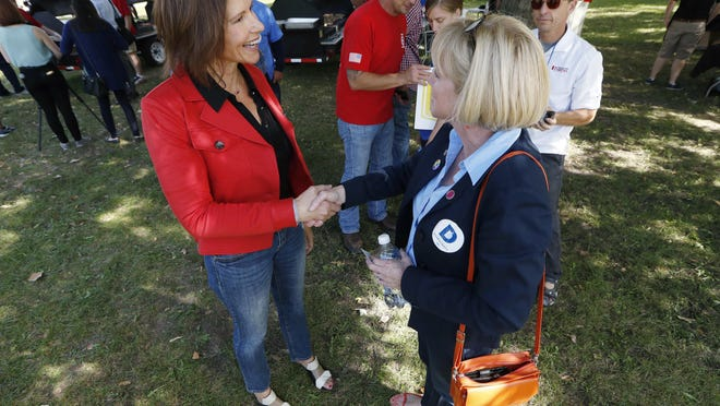 U.S. Rep. Cheri Bustos, D-Ill., left, talks with Iowa gubernatorial candidate Cathy Glasson during the Polk County Democrats Steak Fry, Saturday, Sept. 30, 2017, in Des Moines, Iowa.