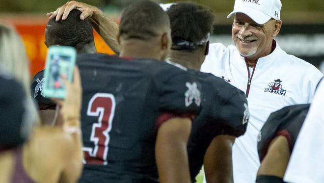 NMSU head coach Doug Martin celebrates with players on Saturday, Sept 23, 2017 as NMSU beats UTEP, 41-14 at Aggie Memorial Stadium.