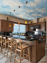 The chef's kitchen has been outfitted with top-of-the-line Viking appliances, and a large granite-topped center island provides ample gathering space.