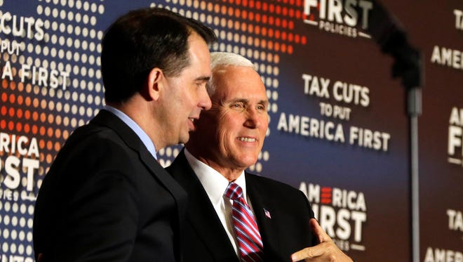 Vice President Mike Pence stands with Wisconsin Gov. Scott Walker. Trump came to Milwaukee Wednesday afternoon to bolster public support for the Republican tax overhaul and raise campaign cash for Walker. He spoke at an event sponsored by America First Policies, a pro-Donald Trump group.
