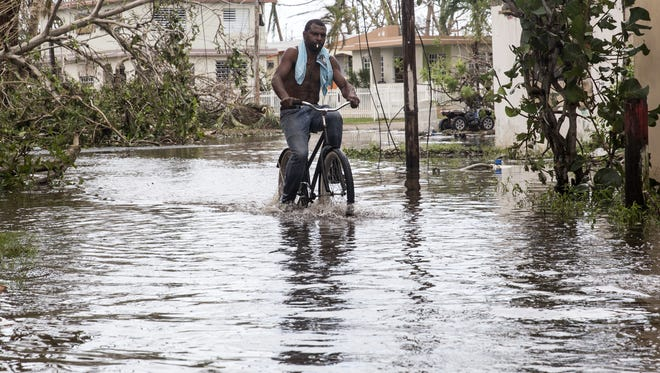 A man rides a bike through high water in Loiza, Puerto Rico, on September 22, 2017 in the aftermath of flooding from Hurricane Maria.