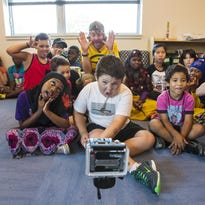 Chris Strub, foreground, visits with kids at the King Street Center in Burlington on Monday. Strub is traveling to all 50 states in 100 days and stopping to do volunteer work at each stop.