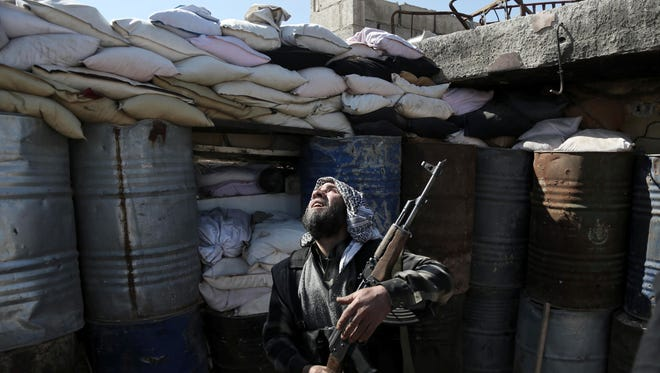 A Syrian rebel fighter from the Islamist Failaq al-Rahman brigade mans a position on the front line against regime forces in the town of Arbin in the eastern Ghouta region on the outskirts of the capital Damascus on Feb. 26, 2016.