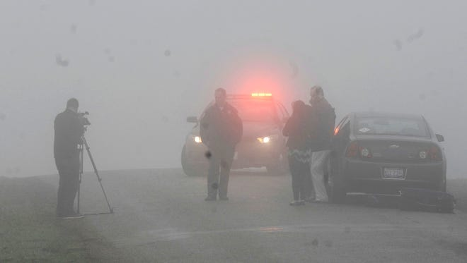 Emergency personnel and media gather at the scene near Bloomington, Ill., where a small plane crashed early Tuesday, April 7, 2015. The Federal Aviation Administration says the Cessna 414 crashed just short of the Bloomington airport after midnight Tuesday while returning from the NCAA college basketball championship in Indianapolis.