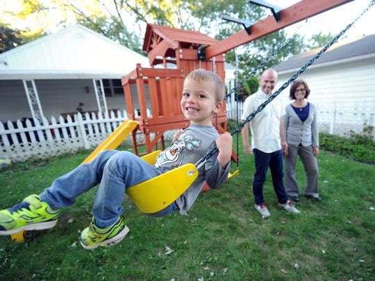 Efrem Kerbel swings in the yard of his De Pere home with with his mom Sarah, right, and dad Andrew looking on.
