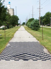 A chessboard illusion on a bike trail in Dysart, painted