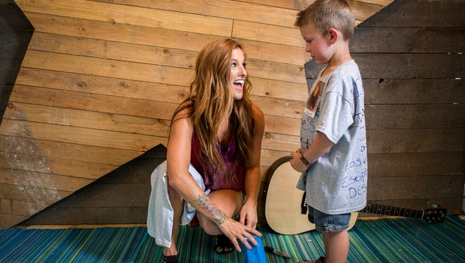 Country artist Cassadee Pope looks up atGavin Bender, 4, of Delmar, as she opens a gift from him Friday at the Big Barrel Country Music Festival.