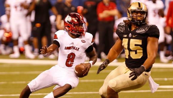 Louisville quarterback Lamar Jackson runs away from